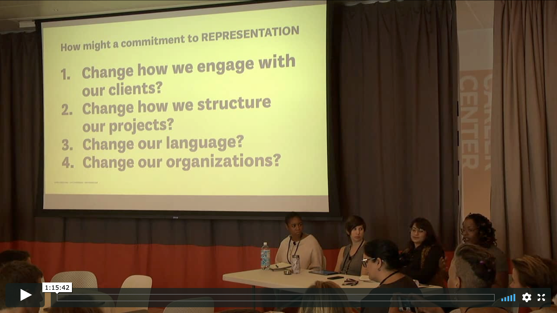 Four panelists sit at a table to the right of a screen showing a presentation on Representation
